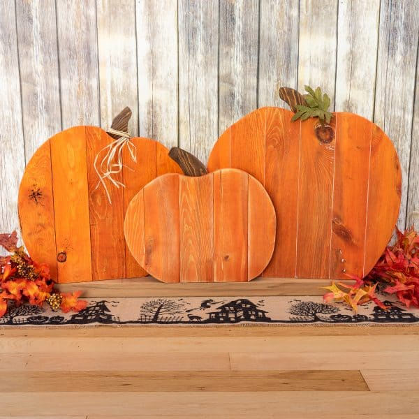 pallet pumpkin trio in front of rustic background with faux fall leaves and Halloween table runner