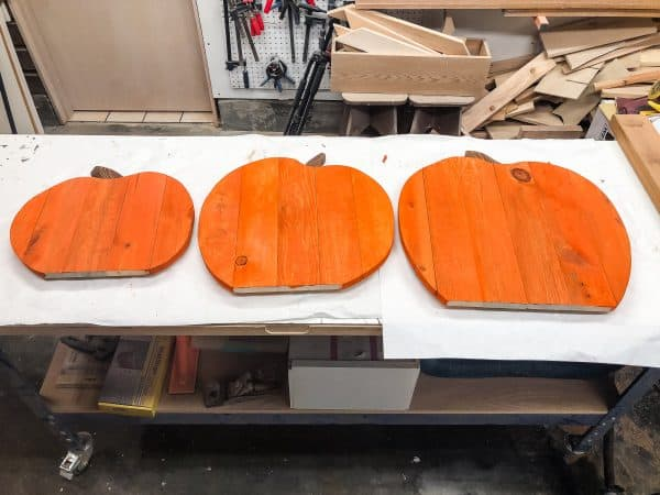 three pallet pumpkins set on a workbench to dry after applying orange wood dye