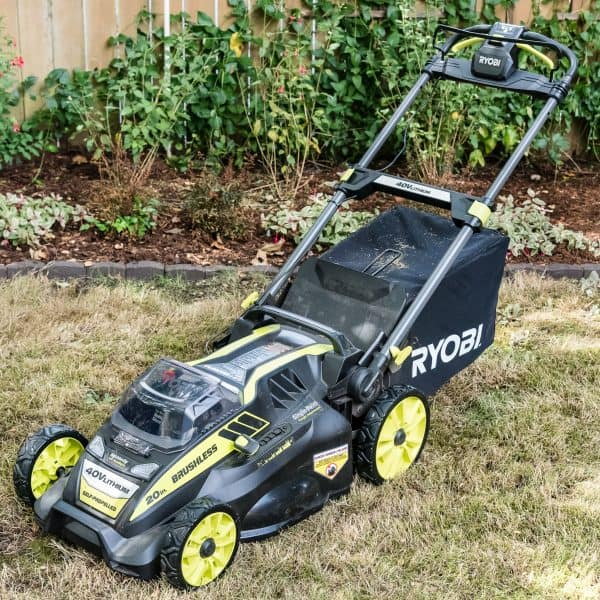 Ryobi self propelled electric lawn mower in front of garden bed