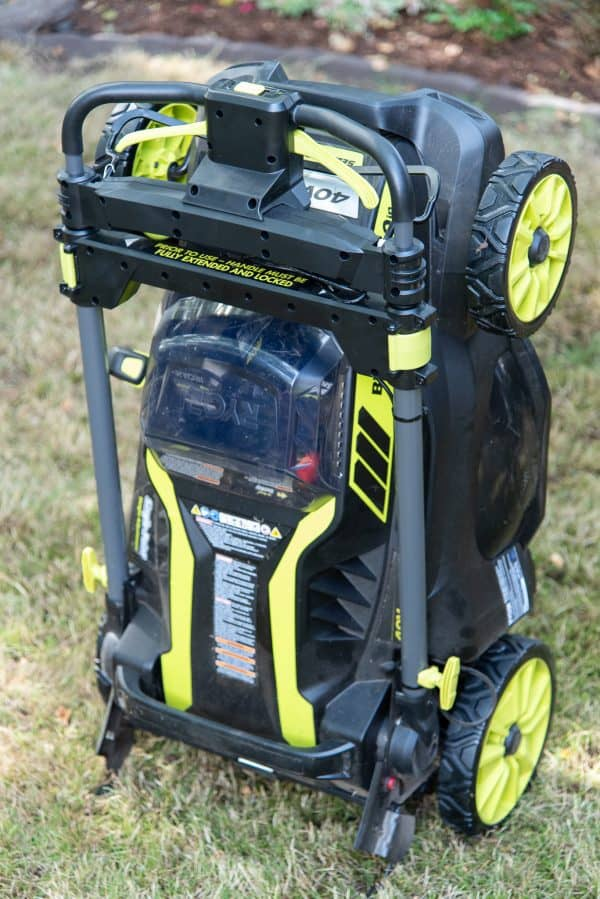 ryobi self propelled electric lawn mower folded up and ready for storage