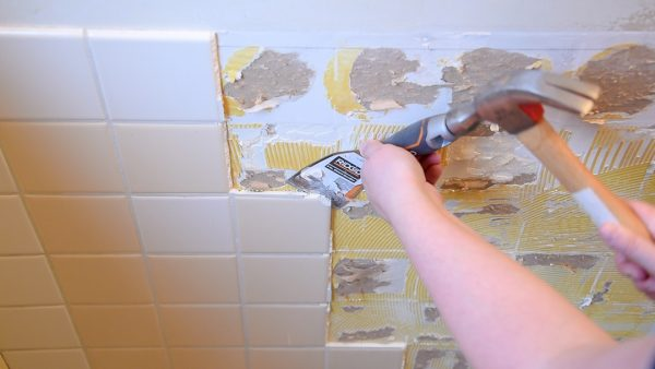 removing wall tiles with a scraper chisel and a hammer