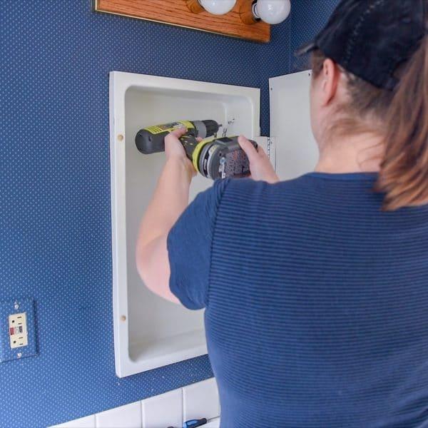 Removing screws from inside of medicine cabinet