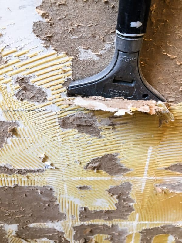 scraper removing tile adhesive from walls