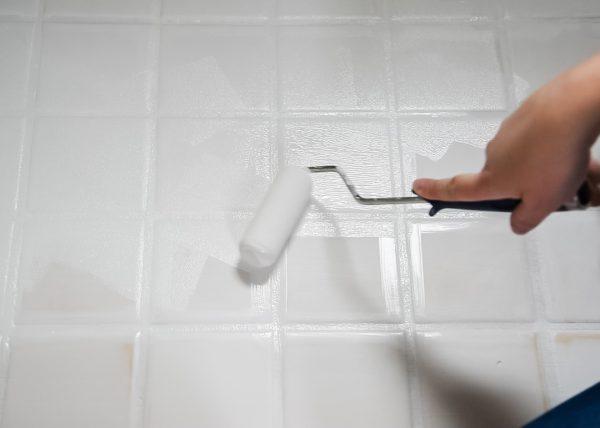 foam roller painting a tile floor