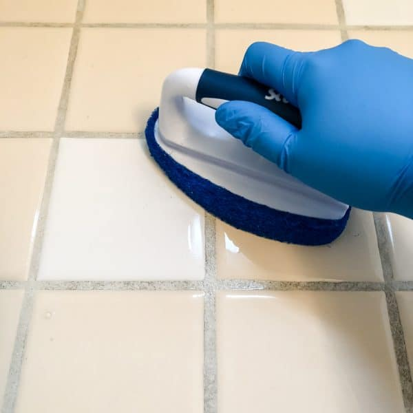 scrubbing tile floor with scrub brush