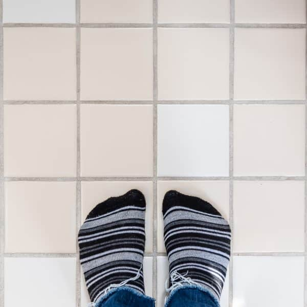 tan and white tiles with feet in striped socks