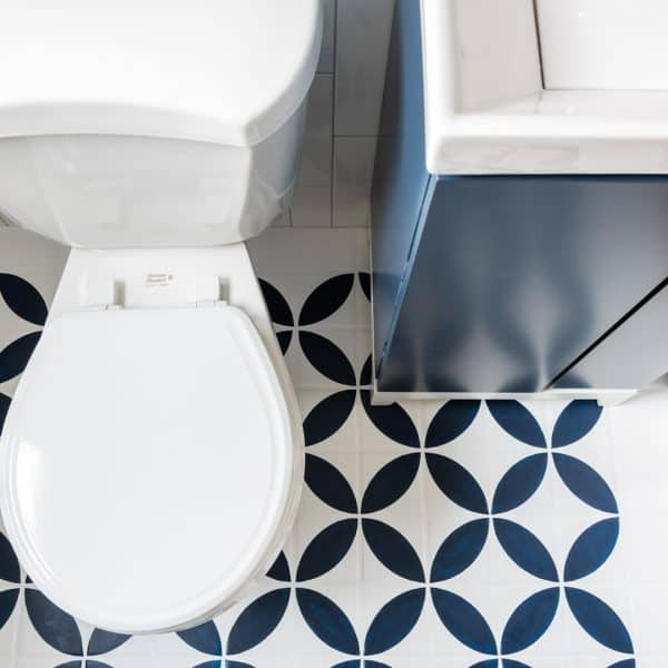 toilet and vanity with bold patterned tile floor