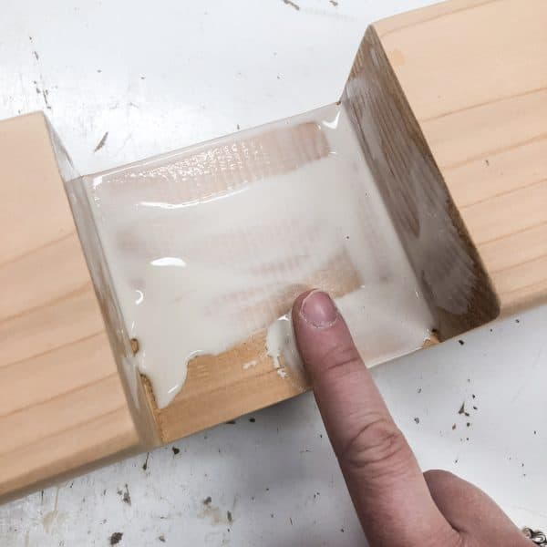 applying wood glue to inside of half lap joint with a finger