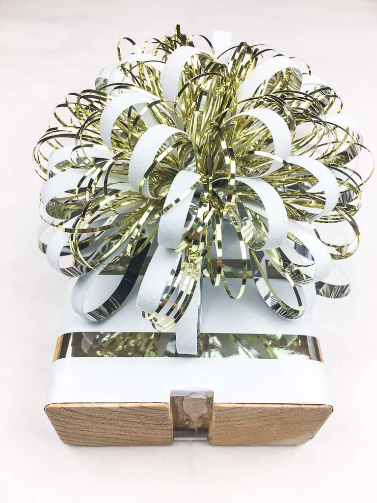 wood block covered in wrapping paper and topped with white and gold bow