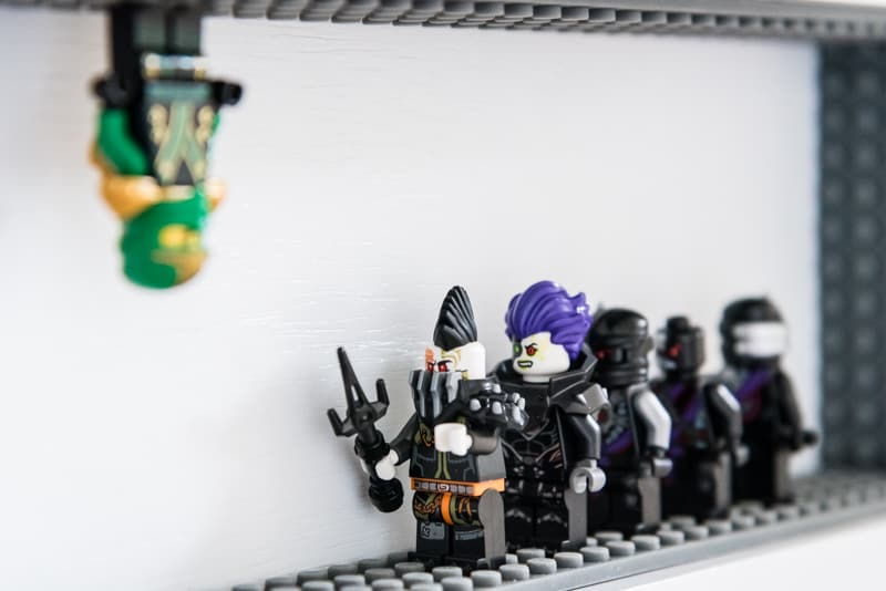 Lego minifigure hanging from top of DIY Lego minifigure display case shelf