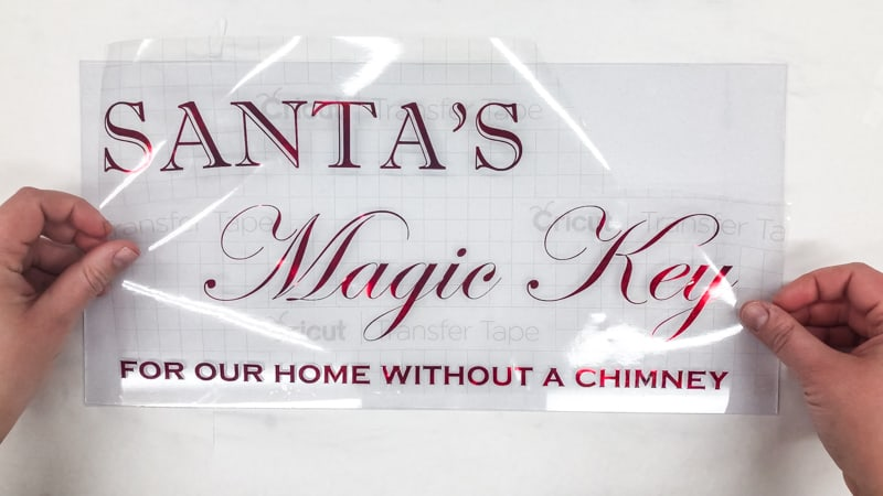 Applying Santa's Magic Key lettering to picture frame glass with transfer tape