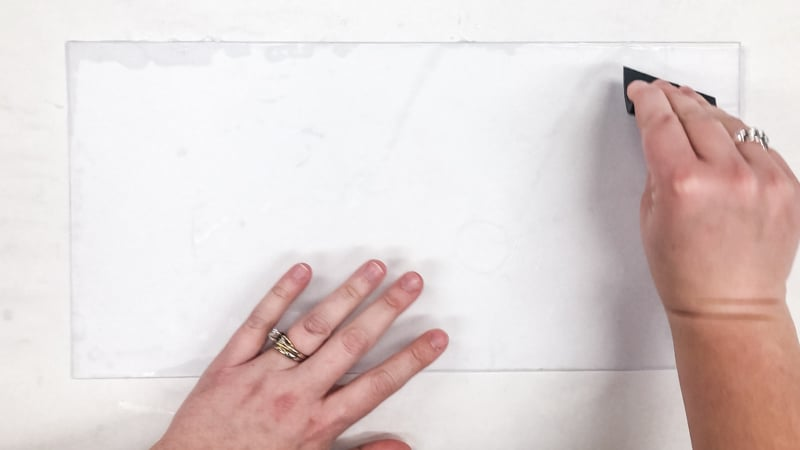 smoothing out air bubbles under contact paper with a scraping tool