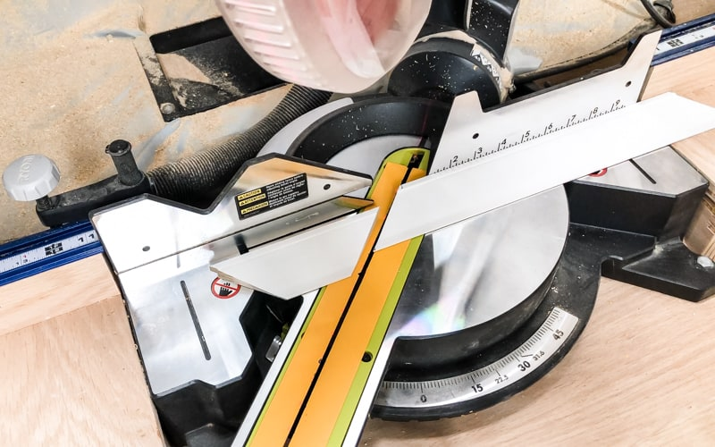 cutting trim at a 45 degree angle on a miter saw to frame an entryway mirror