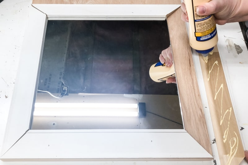 applying wood glue to the back of trim for entryway mirror