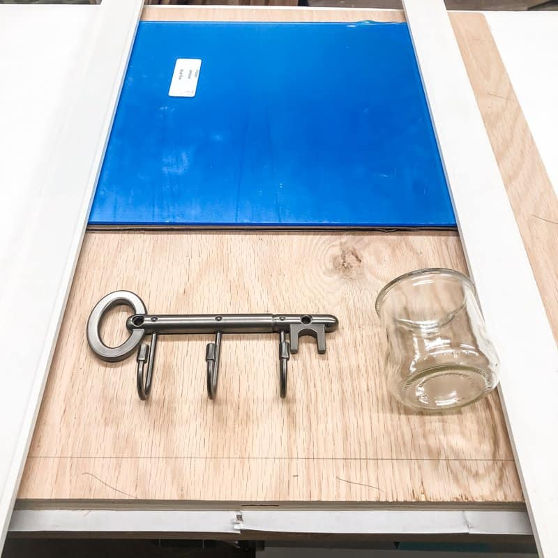 entryway mirror with key hooks and small jar on plywood