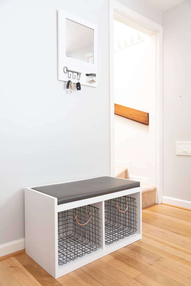 Entryway drop zone by stairs with bench and entryway mirror