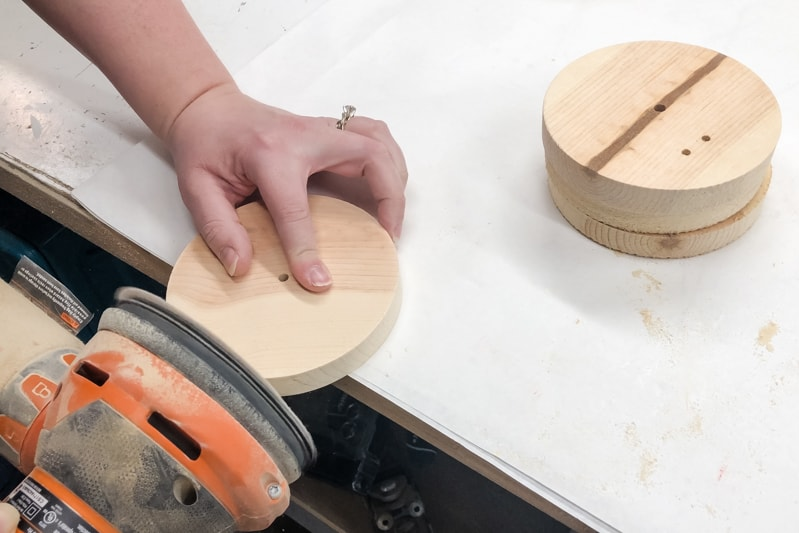 "sanding the cut edge of 5"" wooden circles for IKEA Lego table hack"