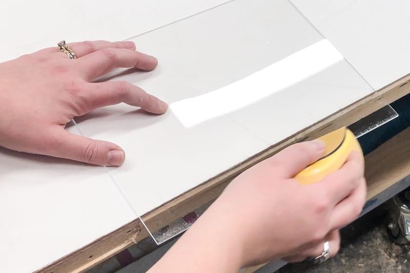 sanding the cut edge of an acrylic sheet