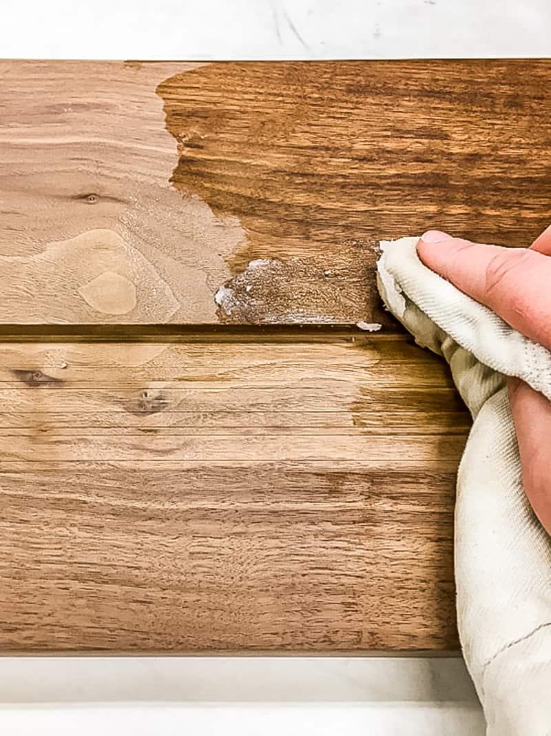 applying cutting board wax to walnut cutting board with a cloth
