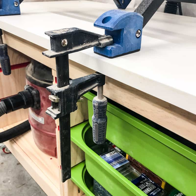 router table clamped to base of router table stand