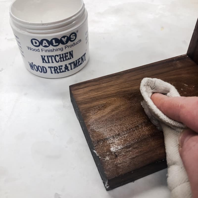 applying cutting board wax to surface of DIY spice rack