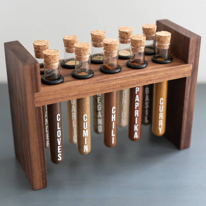 DIY spice rack with test tubes suspended from walnut frame