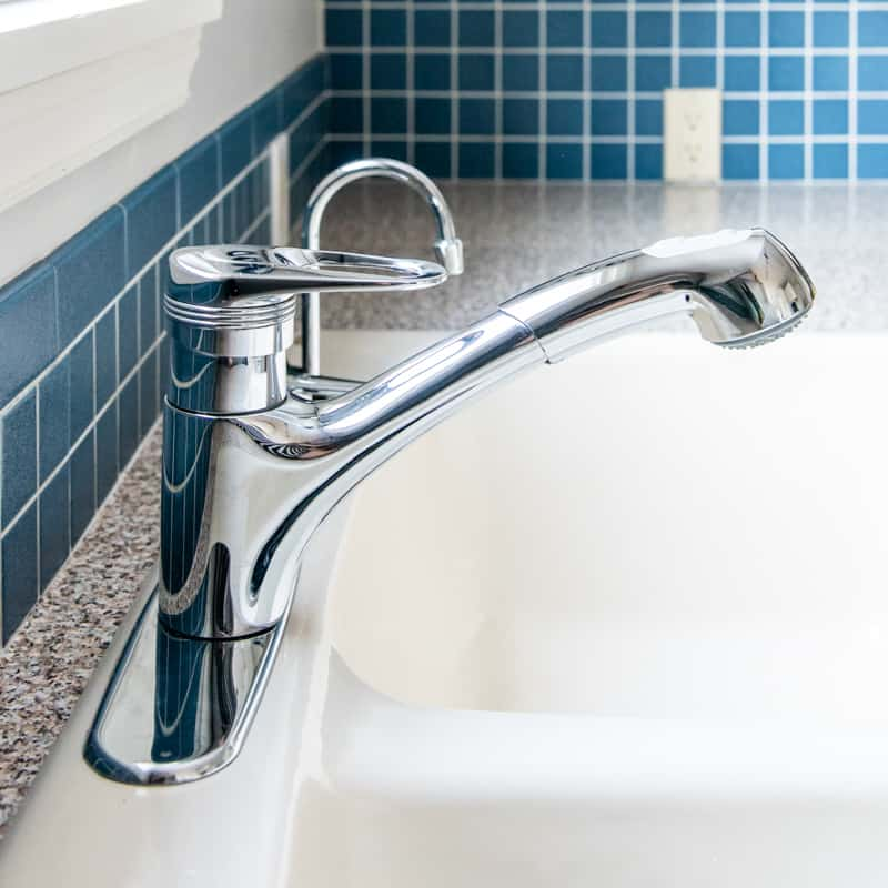old kitchen faucet on almond colored sink with blue backsplash
