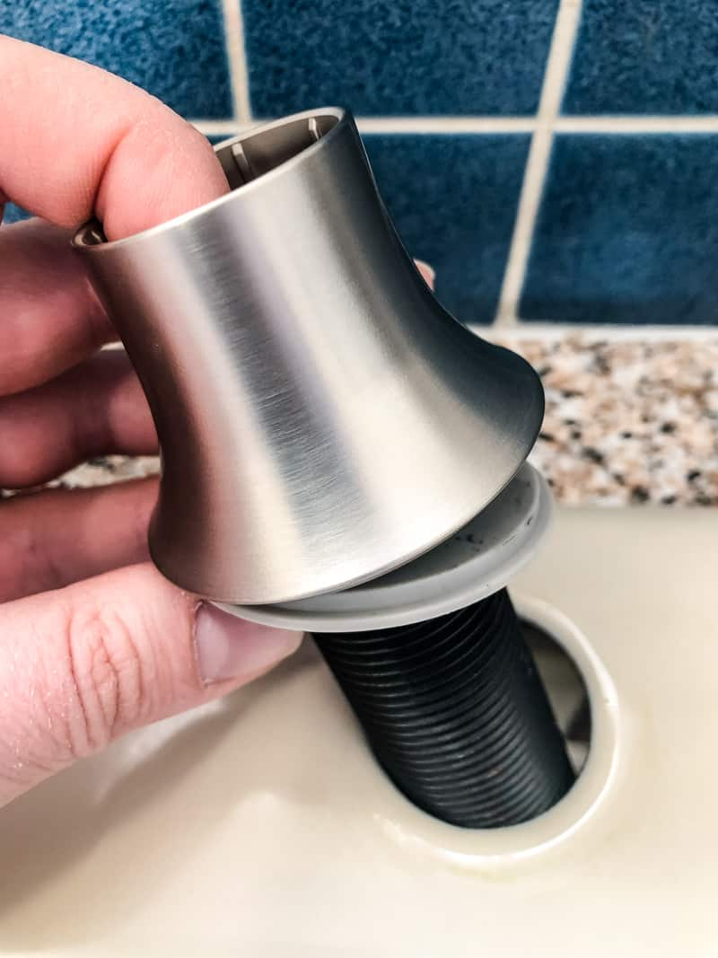 dropping new soap dispenser into kitchen sink hole