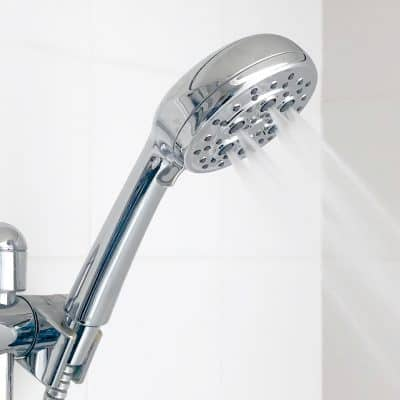handheld shower head in bracket turned on