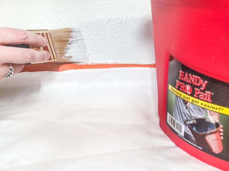 painting edge of baseboards above painter's tape with paint brush with HANDy PRO Pail in foreground