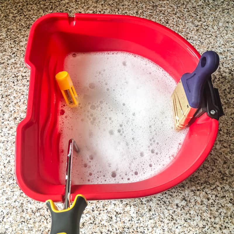 HANDy PRO pail filled with soapy water with paint brush bristles and roller submerged