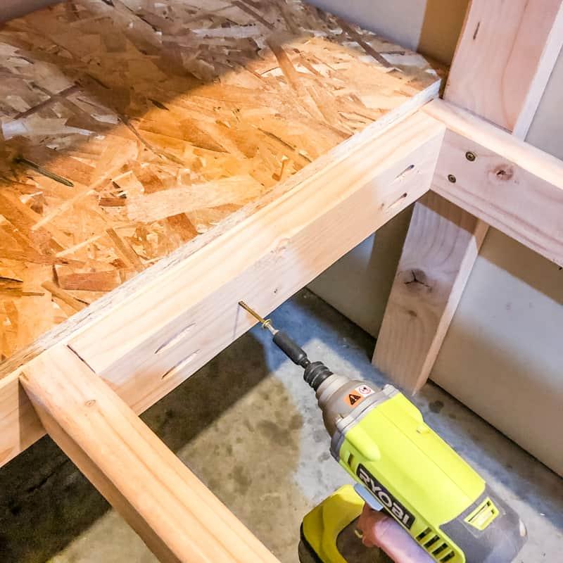 screwing two sets of DIY garage shelves together to form corner storage shelves