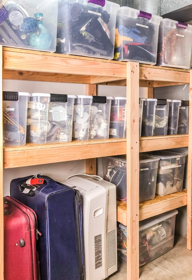 DIY garage shelves filled with plastic bins and suitcase storage underneath