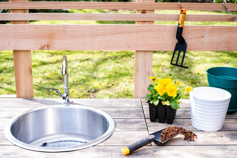 potting bench sink with flowers and gardening tools