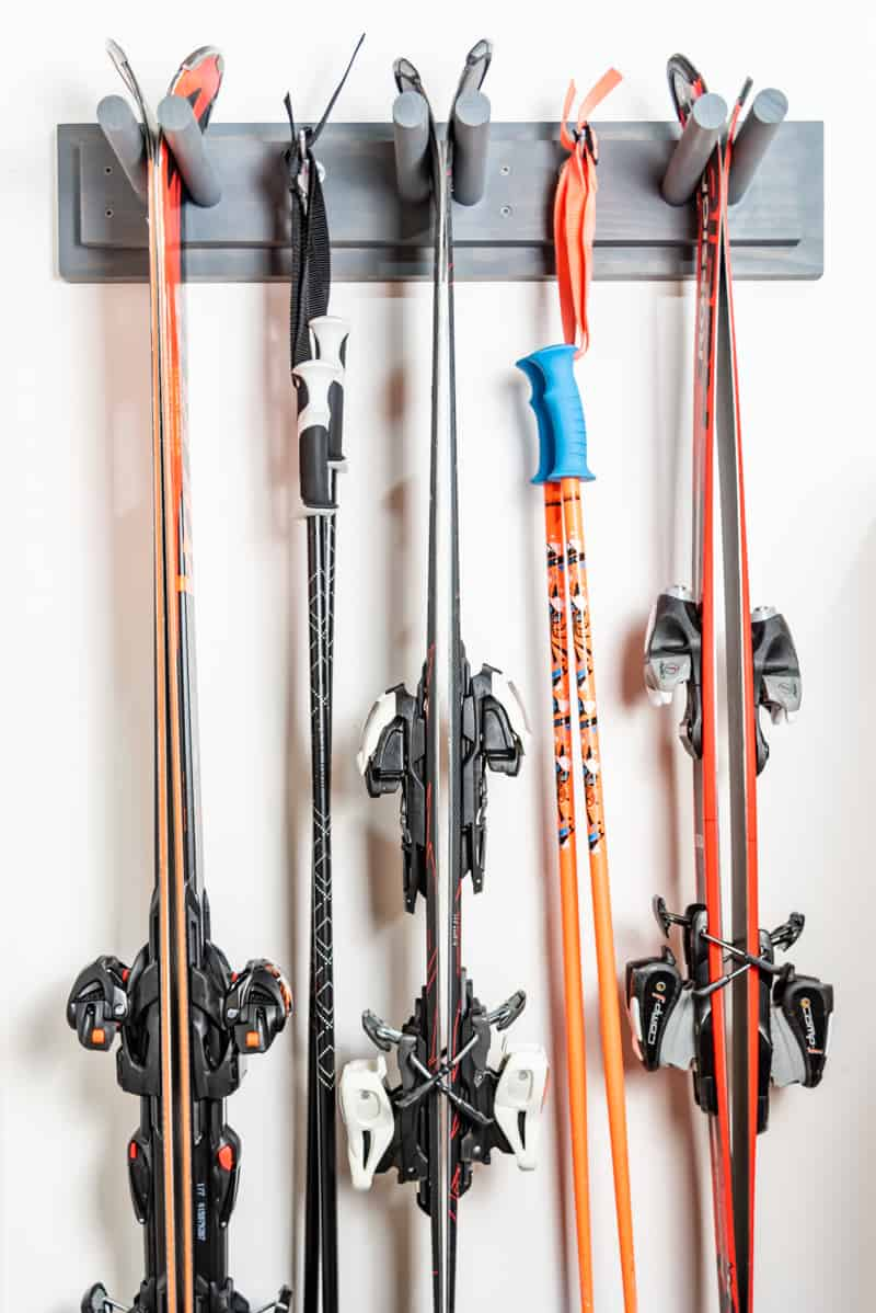 DIY ski rack with three sets of skis and two sets of poles on garage wall