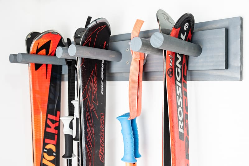 side view of DIY ski rack with three sets of skis and two sets of poles hanging on a garage wall