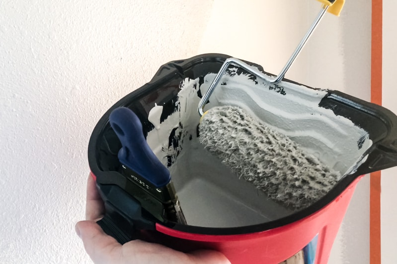 HANDy Pro Pail in hand with paint roller on side