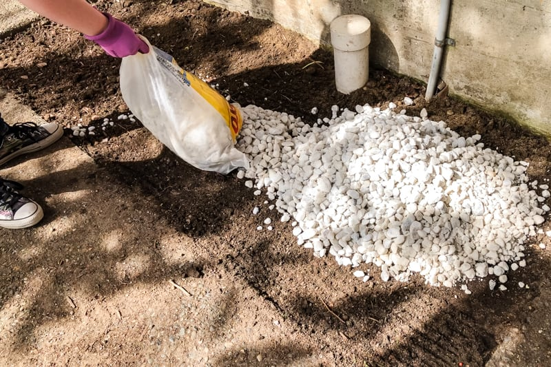 pouring white marble chips from a bag into an empty garden bed