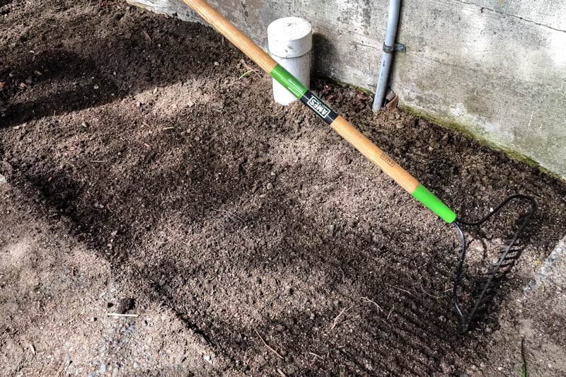 raking empty garden bed before adding white marble chips