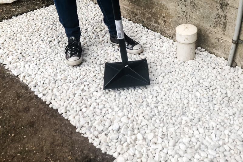 tamping down white marble chips in garden bed
