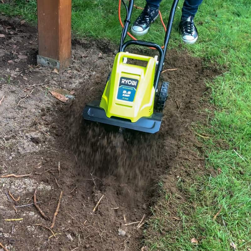 Ryobi cultivator loosening soil for pea gravel patio