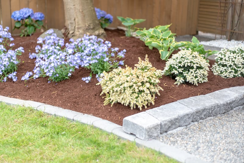 mulched garden bed next to a pea gravel patio with a block retaining wall in between