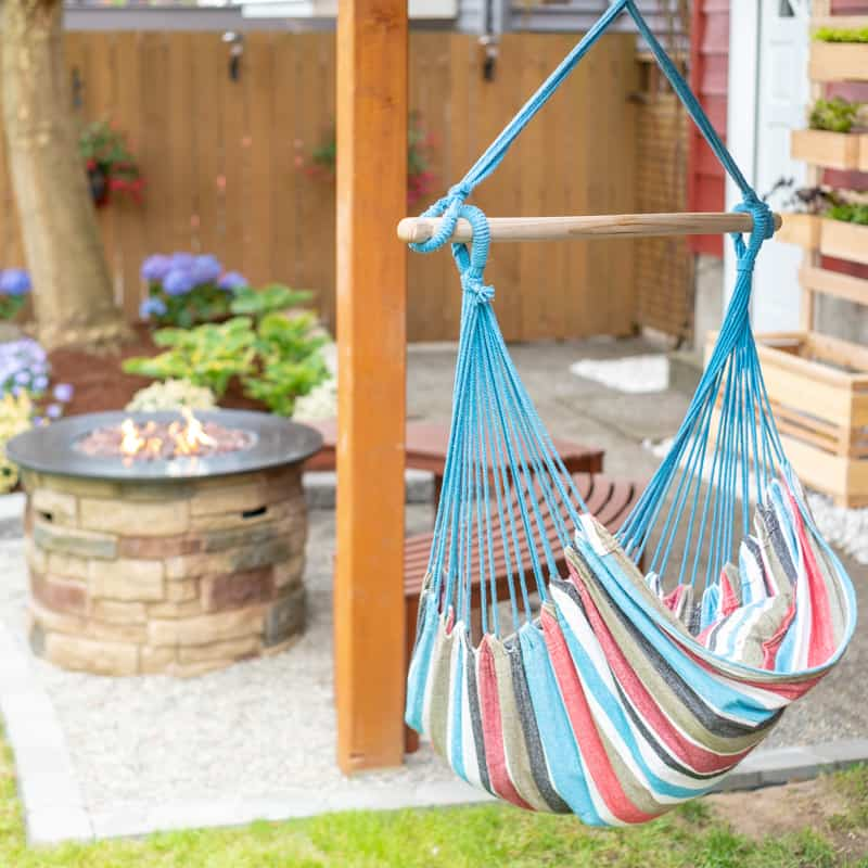 hammock hanging from deck with fire pit and gravel patio in the background