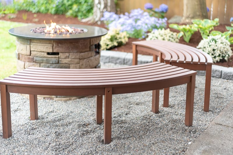 propane fire pit with curved benches on pea gravel patio