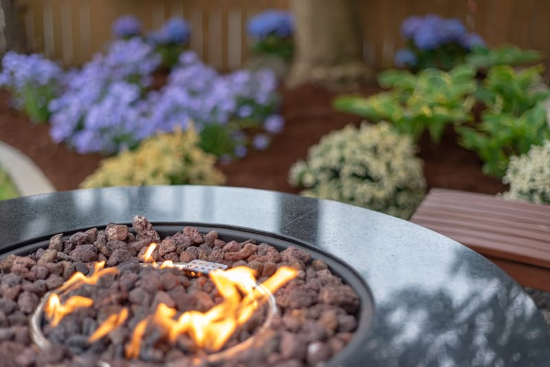 propane fire pit with flower garden in background