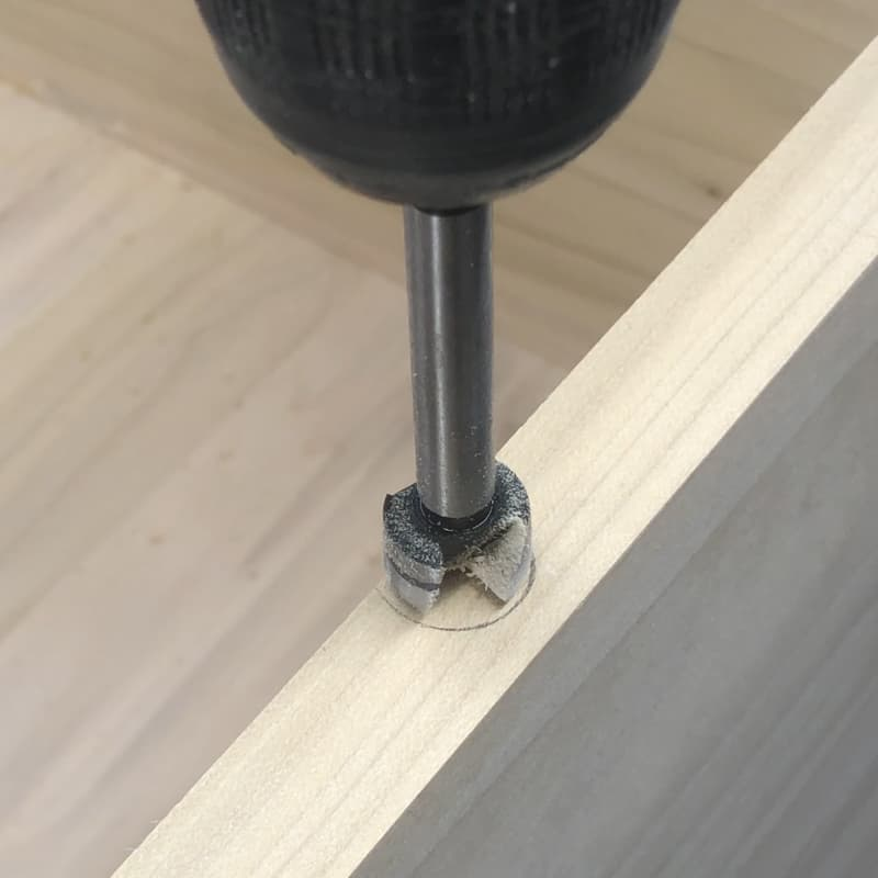 Forstner bit lined up to drill hole for figure 8 fastener