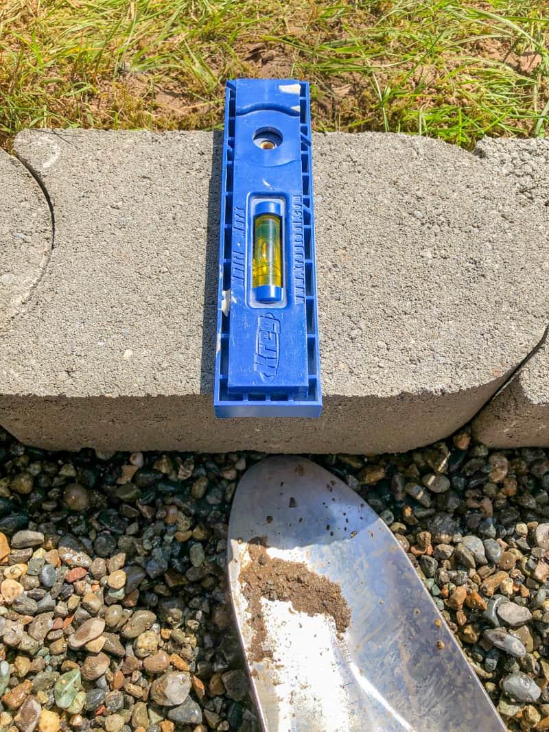 checking level on pea gravel patio border pavers