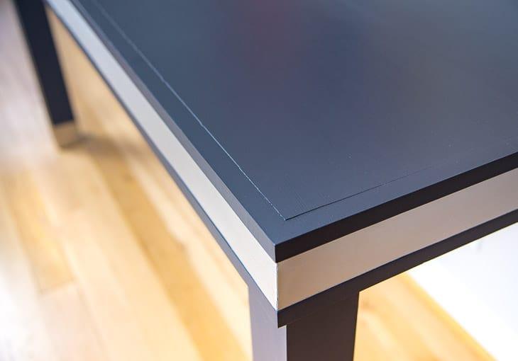 corner of dark blue desk with aluminum band