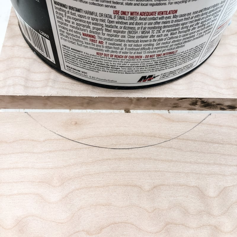 marking the curve of the DIY nightstand drawer pull with a gallon paint can