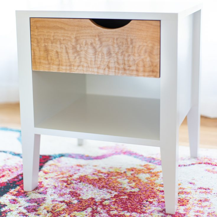 DIY nightstand with white frame and curly maple drawer front on colorful rug